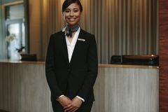 Female concierge ready to welcome guest. Portrait of female concierge standing at hotel reception to welcome guest. Female concierge working in hotel Stock Images