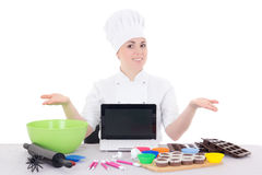 Female confectioner in cook uniform sitting at the kitchen with Stock Image