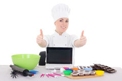Female confectioner in cook uniform sitting at the kitchen with Royalty Free Stock Images