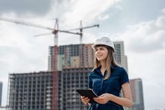 Female construction engineer. Architect with a tablet computer at a construction site. Young Woman looking, building. Female construction engineer. Architect stock images