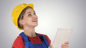 Female construction engineer with a tablet computer at a construction site on gradient background. royalty free stock photo