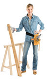 Female Construction With Hand On Hip Holding Plank Of Wood royalty free stock photo