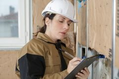 Female construction manager inspecting plasters on wall. Female construction manager inspecting the plasters on the wall royalty free stock photography