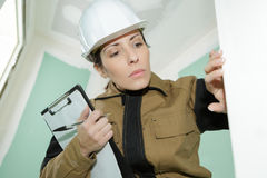 Female construction worker checking finished wall Royalty Free Stock Image