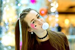 A Female construction worker  a cordless screw gun. Beautiful and shocked or surprised young student girl blowing bubble from chewing gum Stock Photo