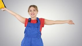 Female construction worker dancing with hardhat on gradient background. stock photography