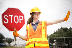 Female Construction Worker Directs Traffic. Female construction apprentice holding a stop sign and directing traffic Royalty Free Stock Photos