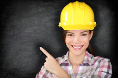 Female construction worker or engineer showing. Pointing at empty blackboard with copy space for your text on chalkboard. Young woman wearing yellow hard hat royalty free stock photo