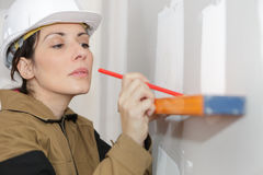Female construction worker holding carefully level. Female construction worker holding carefully a level stock images
