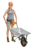 Female construction worker holding a wheelbarrow Royalty Free Stock Photography