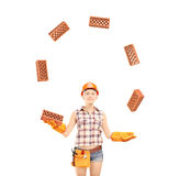 Female construction worker juggling bricks isolated on white bac Stock Image