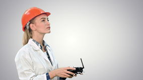 Female construction worker operating a crane using remote control on white background. Female construction worker operating a crane using remote control. Close stock footage