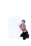 Construction worker pointing at poster. Royalty Free Stock Photography