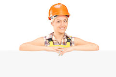 Female construction worker posing behind  panel Royalty Free Stock Photos