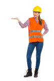 Female Construction Worker Presenting. Young woman in orange reflective vest and yellow hardhat holding hand raised and presenting. Full length studio shot Royalty Free Stock Images