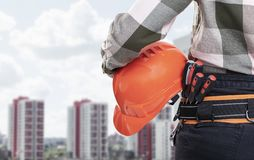 A female construction worker with safety helmet against city background royalty free stock image
