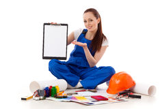 Female construction worker shows blank clipboard. Royalty Free Stock Image