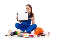 Female construction worker shows blank clipboard. Royalty Free Stock Photo