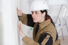 Female construction worker smoothing wall surface. Female Royalty Free Stock Image