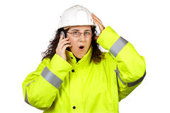 Female construction worker surprised. Calling with phone Royalty Free Stock Image