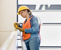 Female construction worker taking measurement Stock Photo