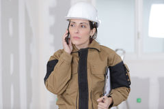 Female construction worker talking on phone on building site Royalty Free Stock Photos