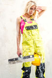 Female construction worker. Tired female construction worker with putty knife working indoors Stock Image