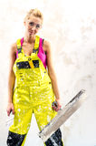 Female construction worker. Tired female construction worker with putty knife working indoors Royalty Free Stock Photography