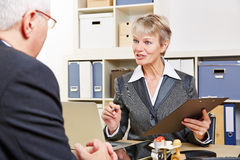 Female consultant in bank talking. Elderly female consultant in bank talking to senior customer Stock Photography