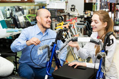 Female consultant offering wheelchair to mature customer. Young female consultant offering wheelchair to mature customer in orthopaedic store. Focus on the man Stock Photo