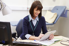 Female Consultant Using Digital Tablet At Desk In Office Stock Photo