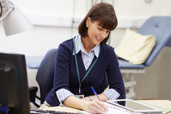 Female Consultant Working At Desk In Office Stock Image