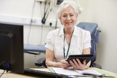 Female Consultant Working At Desk Using Digital Tablet Royalty Free Stock Photos