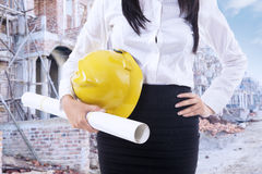 Female contractor with blueprint and helmet Stock Image