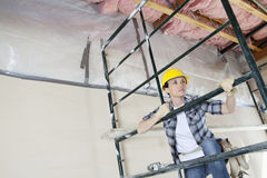 Female contractor climbing scaffold while looking away at construction site Stock Images