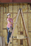 Female contractor climbing up the ladder at construction site Stock Photo