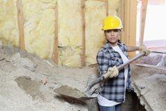 Female contractor digging sand at construction site Stock Images