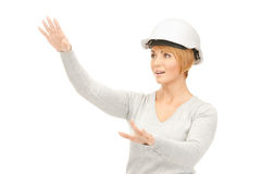 Female contractor in helmet working with something imaginary Royalty Free Stock Photography
