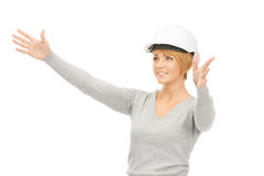 Female contractor in helmet working with something imaginary Stock Images