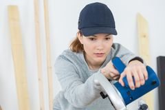 Female contractor lowering circular saw. Circular royalty free stock photography