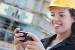 Female Contractor Wearing Hard Hat on Site Texting with Phone Stock Image