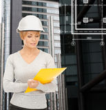 Female contractor in white helmet with files Royalty Free Stock Photography