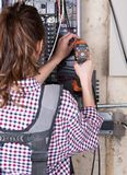Female contractor worker holds cordless drill gun. At construction site Royalty Free Stock Image