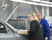 The female controler checks quality of polishing of a body of th. E car. Car assembly enterprise Stock Photography