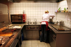 Female cook in action. In the kitchen of a fast food restaurant stock photo