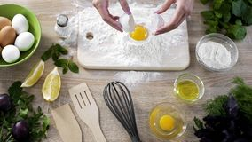 Female cook adding egg in flour, preparing dough for making homemade pancakes stock photos