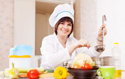 Female cook adds salt or spices into  pan Royalty Free Stock Images
