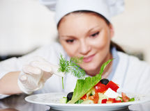 Female cook chef decorating prepared salad food Royalty Free Stock Photos