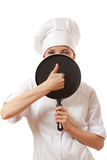 Female cook / chef in white uniform with pan Royalty Free Stock Photography