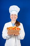 Female cook with cookie over blue Royalty Free Stock Photography